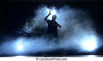 One hip hop break-dancer stylish man in sunglasses dancing, smoke, silhouette, slow motion