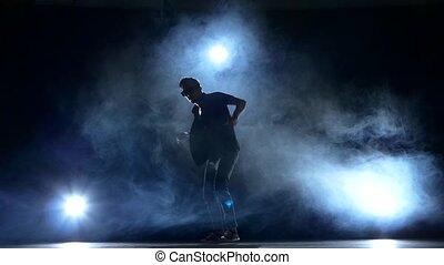 One hip hop break-dancer stylish man in sunglasses starts  dancing, smoke, silhouette, slow motion