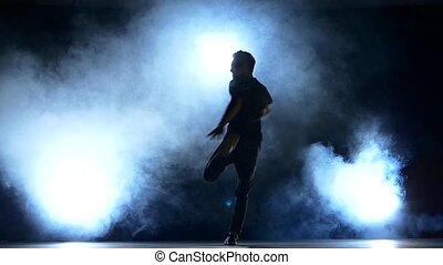 One hip hop break-dancer stylish man starts dancing, smoke, silhouette, slow motion