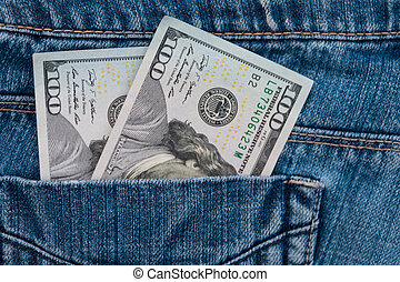 One hundred American dollars bills in the pocket of blue jeans