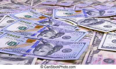 One Hundred Dollar Bills Fall on the Table with American Dollars of Different Denominations