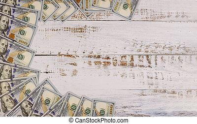 One hundred dollar bills on wooden background.