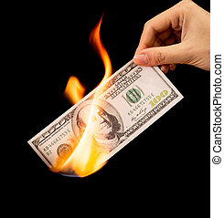 One hundred dollars burn in the hand on a black background