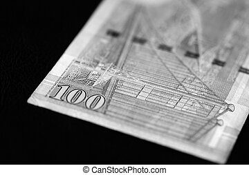 One hundred Hong Kong dollars banknote on a dark background close up. Black and white