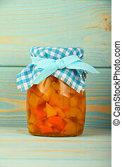 One jar of quince jam at blue vintage wood surface - Close...