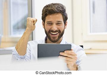 One joyful man holding digital tablet