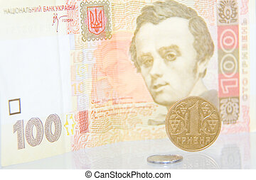 One kopek and hrivna coins against one hundred bill. You must save every coin to get more money. Ukrainian currency.