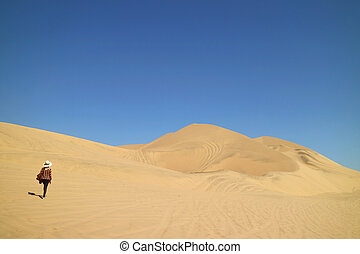 One lady walking on the incredible sand dunes of Huacachina desert in Ica region of Peru, South America