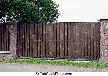 one large brown wooden gate on a rural street