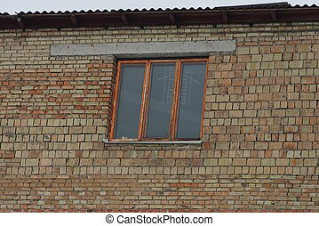 window on a brown wall of a building on the street