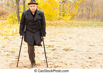 One-legged man walking with crutches in the park - Lonely...