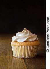 One lemon sponge cup cake with meringue topping isolated on wooden table close up - food background