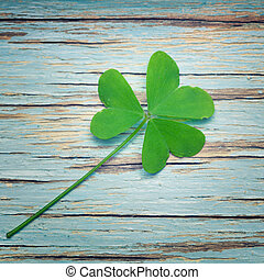 One lucky clover on a blue vintage wood background