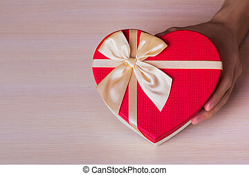 One male hand holding red gift box in shape of heart
