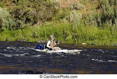 one man alone on a river fishing in a kayak