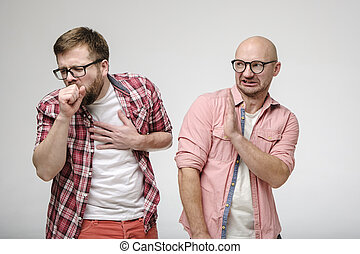 One man coughs, closing mouth with hand, and other man makes a gesture of protection, putting palm forward and looking in disgust.