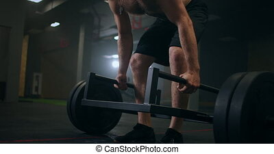 One Man Lifting Heavy Weights In Gym. Romanian deadlifts with a barbell in gym in slow motion. High quality 4k footage