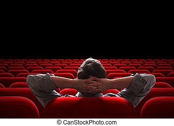 one man sitting in empty cinema or theater auditorium