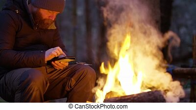 One man using compass and smart phone by campfire in the forest