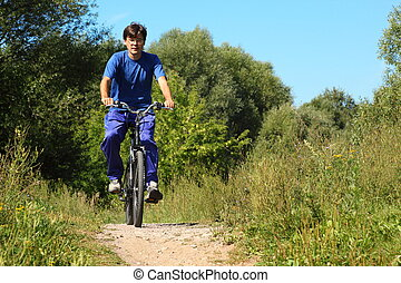 one man wearing sporty clothes is riding on a bycicle. summer day.