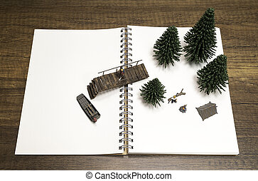 One miniature walking on bridge to boat and the other in camp fire on notebook