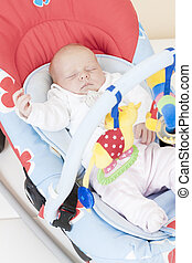 one month old baby girl sleeping in baby's chair