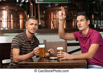 One more beer please! Two friends drinking beer at the pub while one of them asking a waiter.