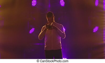 One musician plays the trumpet. A talented man performs a melody of classical instrumental music with dramatic emotions in the stage light darkness of the studio. Slow motion. Close up
