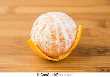 One navel orange peeled isolated on wood background