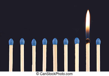 One flame amongst a row of unlit matches