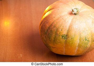 One orange pumpkin on a wooden table
