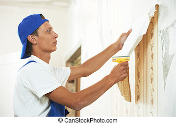 One painter worker peeling off wallpaper during interior home repair renovation work