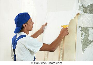 painter worker peeling off wallpaper - One painter worker...