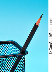 One pencil in a wire mesh pencil holder, Blue background