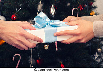 One person giving a christmas gift to another