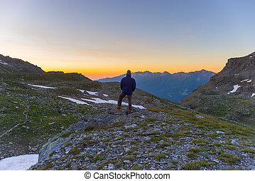 One person looking at colorful sunrise high up in the Alps. Wide angle view from above with glowing mountain peaks in the background. Summer adventure and exploration.