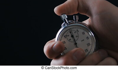 One person starting up a stopwatch at black background - ...