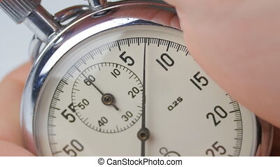 One person starting up a stopwatch at white background - ...