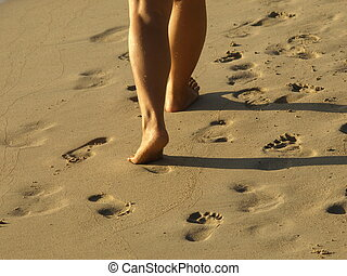 one person walking in sand near the sea shore