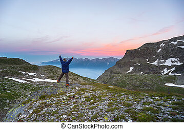 One person watching sunrise high up in the Alps - One person...