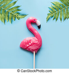 One pink flamingo candy lollipop with tropical fern on blue. Top view. Fun minimal vacation concept.
