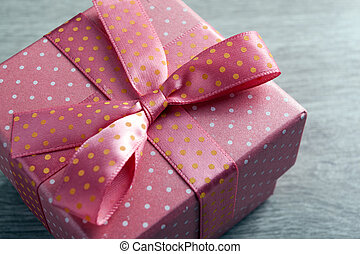 pink gift box with a bow on a gray wooden background