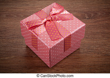 pink gift box with a bow on a wooden background