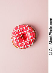 One pink live colar donut with heart shaped sprinkles on pink background, monochrome seet unhealthy food, love, valentine day concept, flat lay, top view, copy space