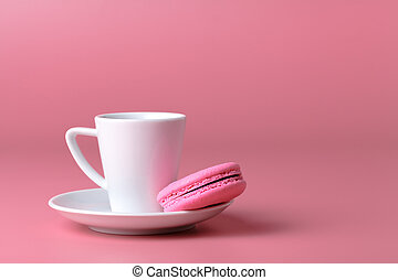 One pink macaroon with cup of coffee