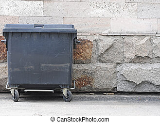 one plastic garbage can with wheels and folding lids. Near ragged wall.