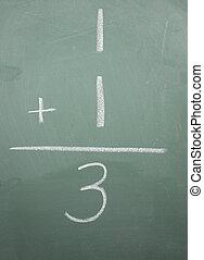 One plus one equals three written on a blackboard.