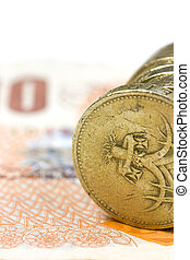 One pound coins on the edge on a white background