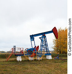 One pump jacks on an oil field. Autumn