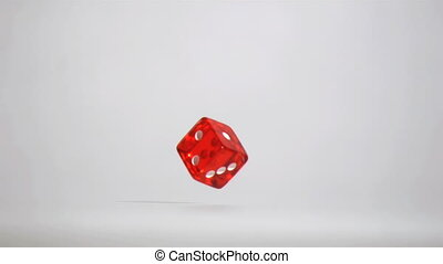 One red dice in super slow motion turning near the floor